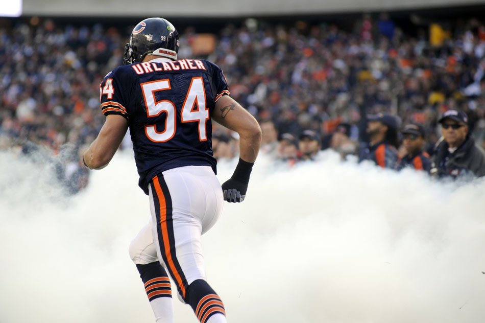 Chicago Bears linebacker Brian Urlacher (54) runs onto the field through smoke during player introductions before a game on Sunday, Nov. 28, 2010, at Soldier Field in Chicago.