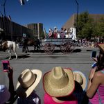 A family watches as a covered wagon passes the intersection of Capitol Avenue and 21st Street during the Cheyenne Frontier Days parade on Saturday, July 23, 2011, in downtown Cheyenne. (James Brosher/Wyoming Tribune Eagle)