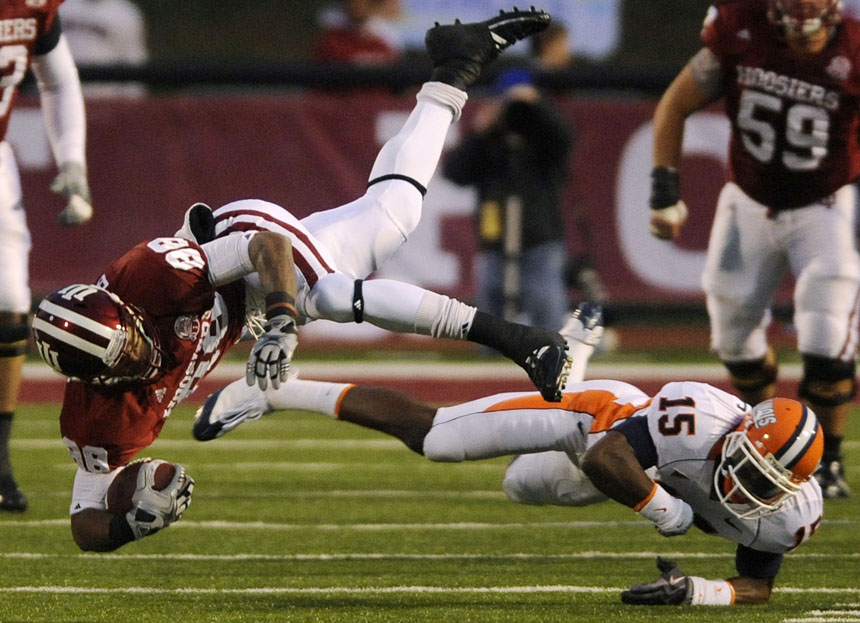 IU wide receiver Damarlo Belcher tumbles to the ground with the ball after a tackle by Illinois cornerback Walter Aikens during a football game on Saturday, Oct. 17, 2009, at Memorial Stadium. IU won 27-14.