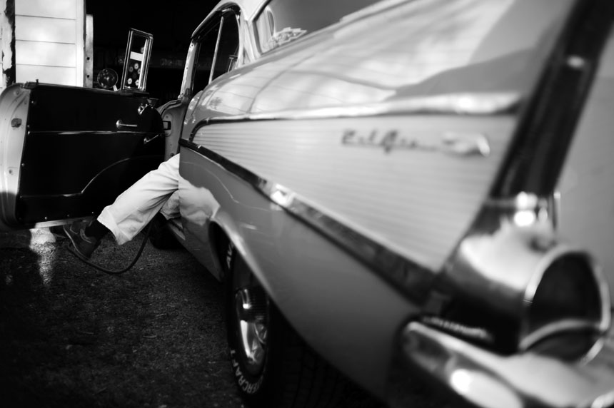 Tom Brosher dangles a leg outside of his 1957 Chevy Bel Air as he looks to cut a hole in the floor of the car for the shifter of his new 5-speed manual transmission on Thursday, May 6, 2010, in Dunkirk, Ind.