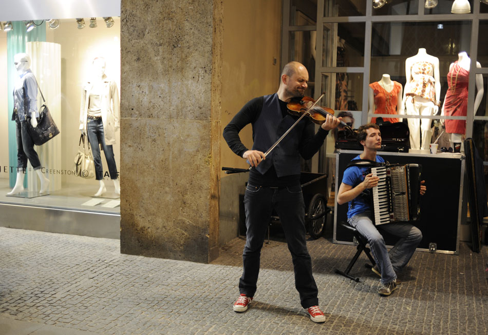 Violinist Igor Stravansky, of the group Konnexion Balkon, performs for pedestrians outside a clothing store on Monday, May 24, 2010, in Munich, Germany.