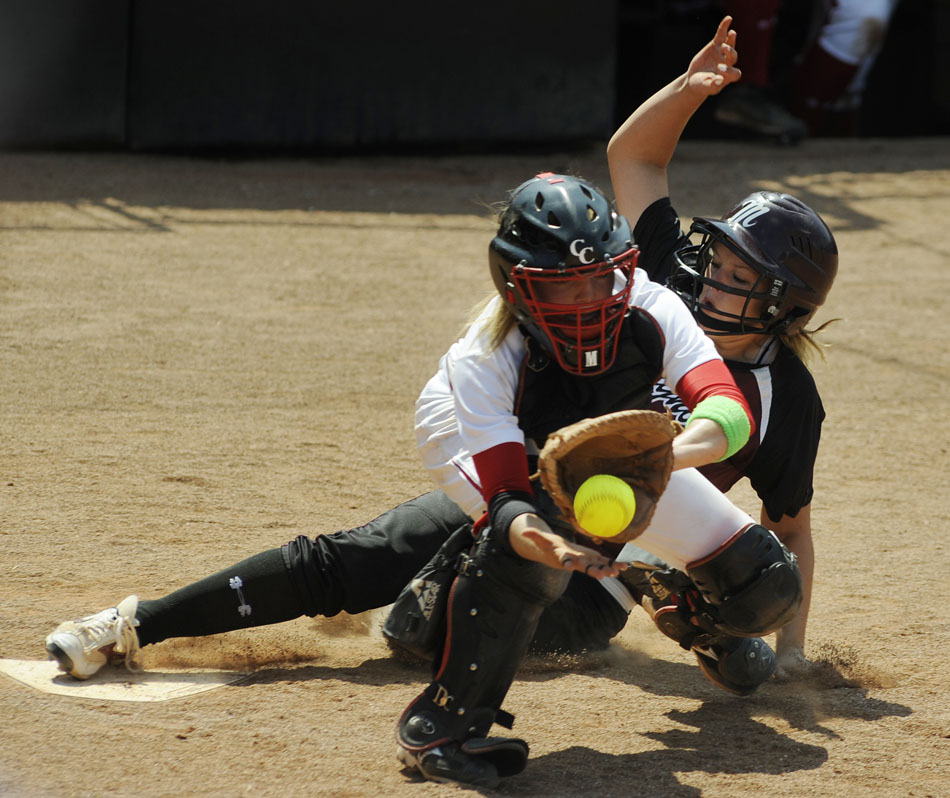 Magnolia's Madison Kraatz slides safely into home just in front of a throw to Canyon catcher Mandy Ogle in the top of the 10th inning during the UIL 4A softball semifinal at the University of Texas on Friday, June 4, 2010. Kraatz's score was the first of the game as Magnolia won 2-0 to advance to Saturday's 4A championship game.