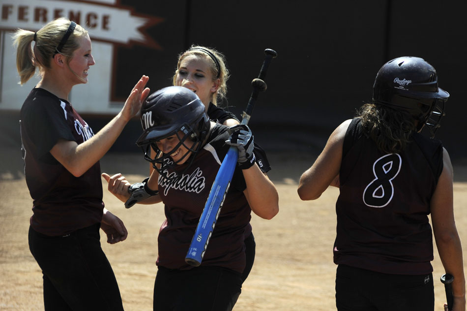 A Magnolia player is congratulated by her teammates after she scored the team's second run in the top of the 10th inning in a 4A softball semi-final against Canyon at the University of Texas on Friday, June 4, 2010.