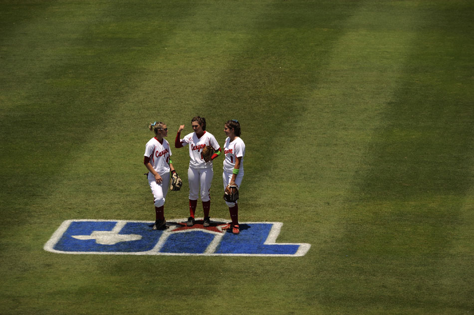 Canyon players Kailee Vrana, left, Chelsey Fisher and Andrea Robson talk in the outfield before the first pitch in a 4A softball semi-final against Magnolia at the University of Texas on Friday, June 4, 2010.