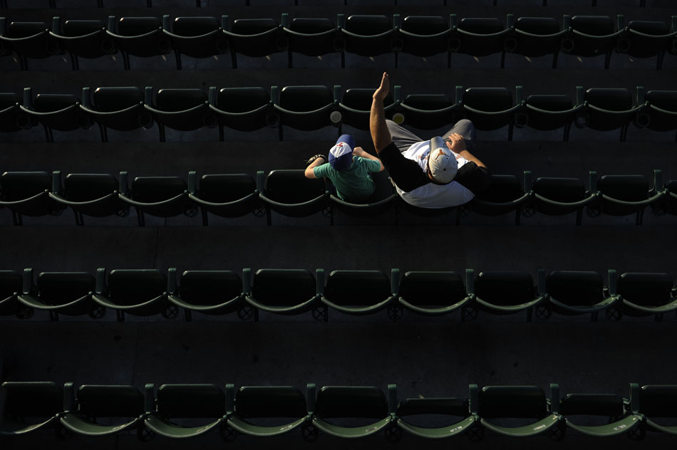 A man shields his eyes from the sun as he watches a minor league baseball game between Round Rock and Omaha at Dell Diamond in Round Rock on Monday, June 21, 2010. The two were some of the only fans to sit looking into the sun on the first base side before sundown.