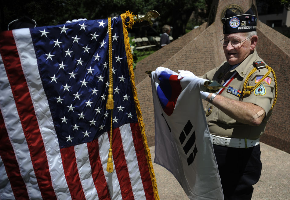 "Andrew ""Buddy"" Blair, a Korean War veteran, rolls up the American flag after a ceremony marking the 60th Anniversary of the start of the Korean War at the Texas Korean War Veterans Memorial on Friday, June 25, 2010."
