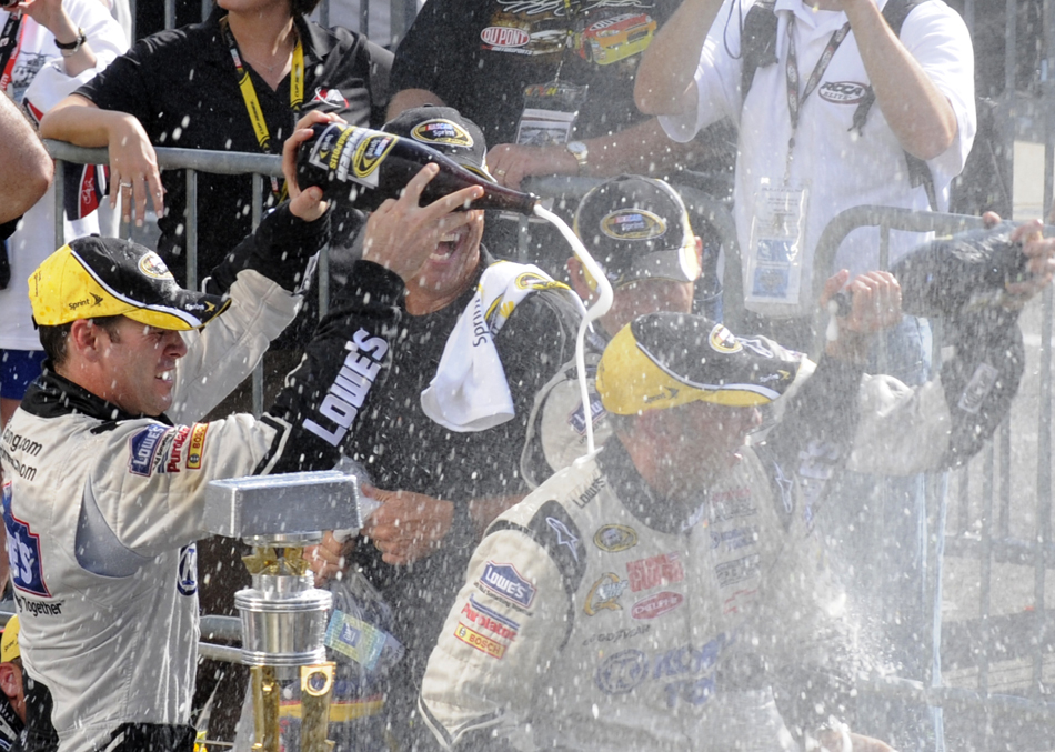 Driver Jimmy Johnson, left, soaks crew chief Chad Knaus with champaign after Johnson's team won the Brickyard 400 on Sunday, July 26, 2009, at the Indianapolis Motor Speedway.