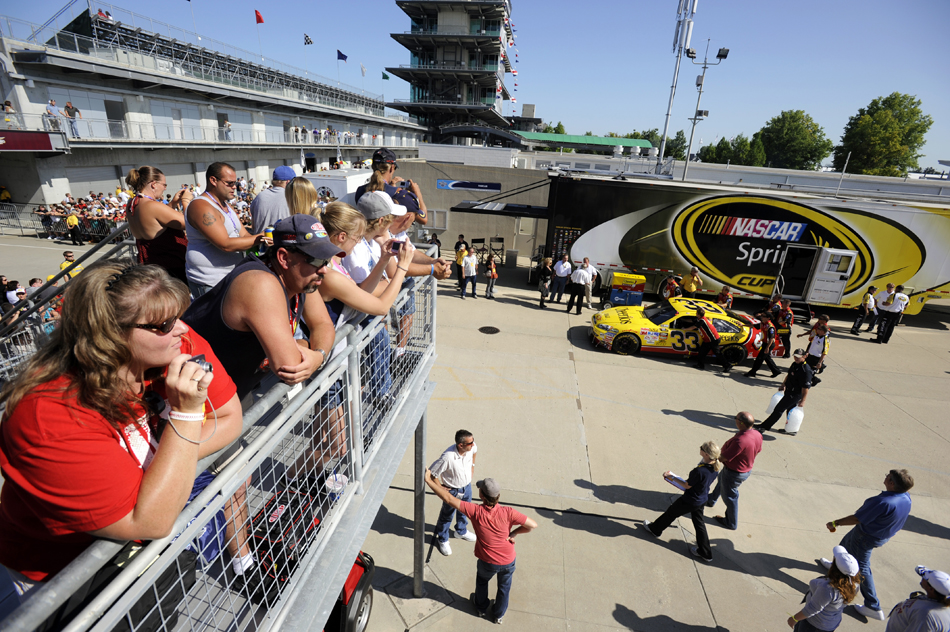 Fans watch as cars, including the No. 33 Clint Bowyer car, are pushed down Gasoline Alley towards pit lane before the start of the Brickyard 400 on Sunday, July 26, 2009, at the Indianapolis Motor Speedway.