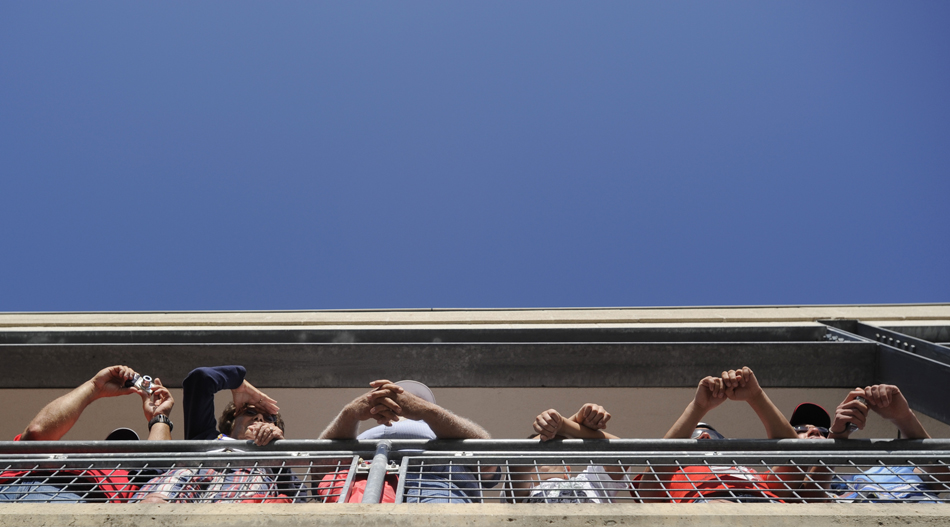 Fans watch from a suite's balcony as crews prepare cars for final inspection before the start of the Brickyard 400 on Sunday, July 26, 2009, at the Indianapolis Motor Speedway.