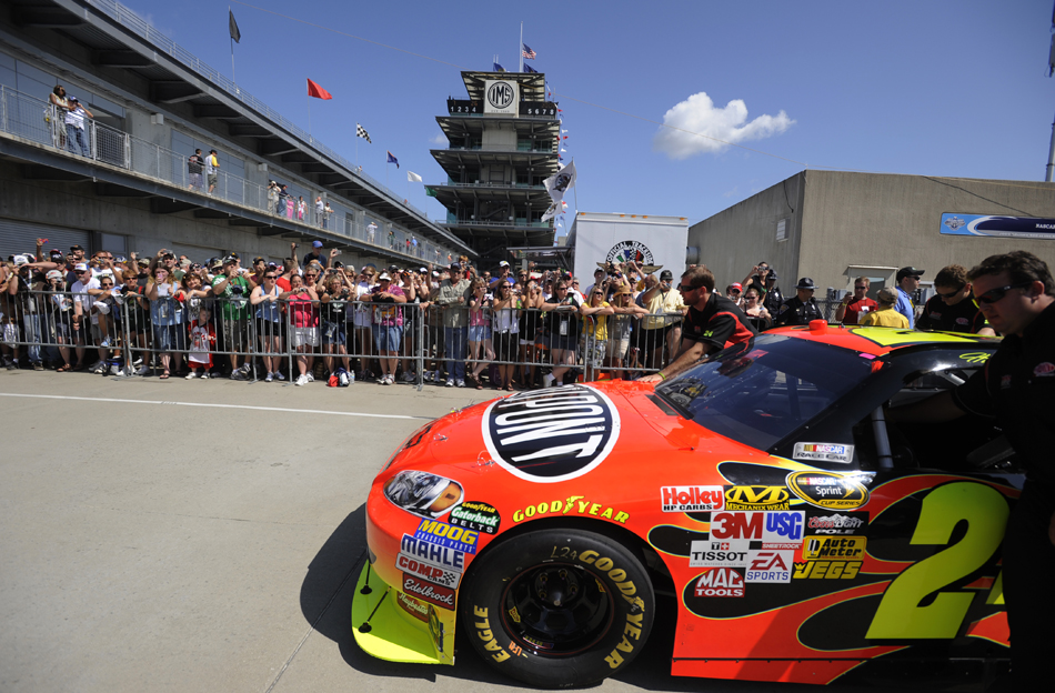 Fans watch as Jeff Gordon's No. 24 Chevrolet makes its way down Gasoline Alley before the start of the Brickyard 400 on Sunday, July 26, 2009, at the Indianapolis Motor Speedway. Gordon qualified 22nd.