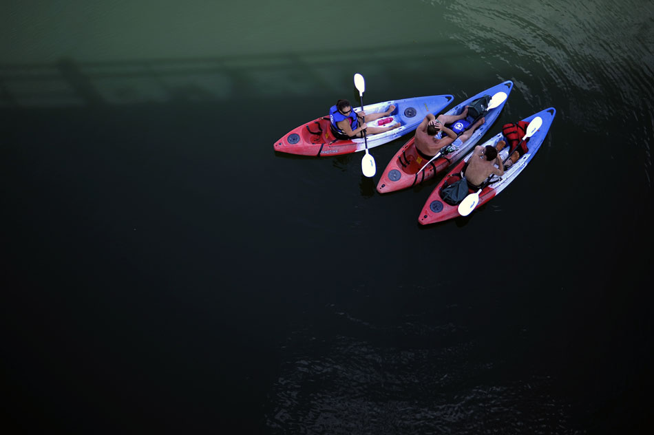 Kayakers take a break in the shade of a bridge on Lady Bird Lake on Sunday, July 18, 2010. Temperatures reached 100 degrees on Sunday.