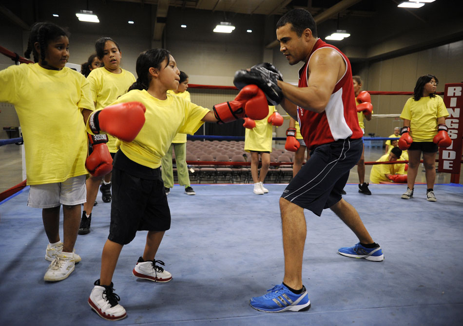 """Alyssa Castillo, age 9, takes a jab at Jesús """" El Matador"""" Chávez during a Police Activities League boxing clinic at the Palmer Events Center on Monday, July 12, 2010."""