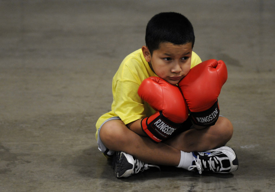 Isaac Hernandez, age 9, watches as an instructor speaks to his group during a Police Activities League boxing clinic at the Palmer Events Center on Monday, July 12, 2010.
