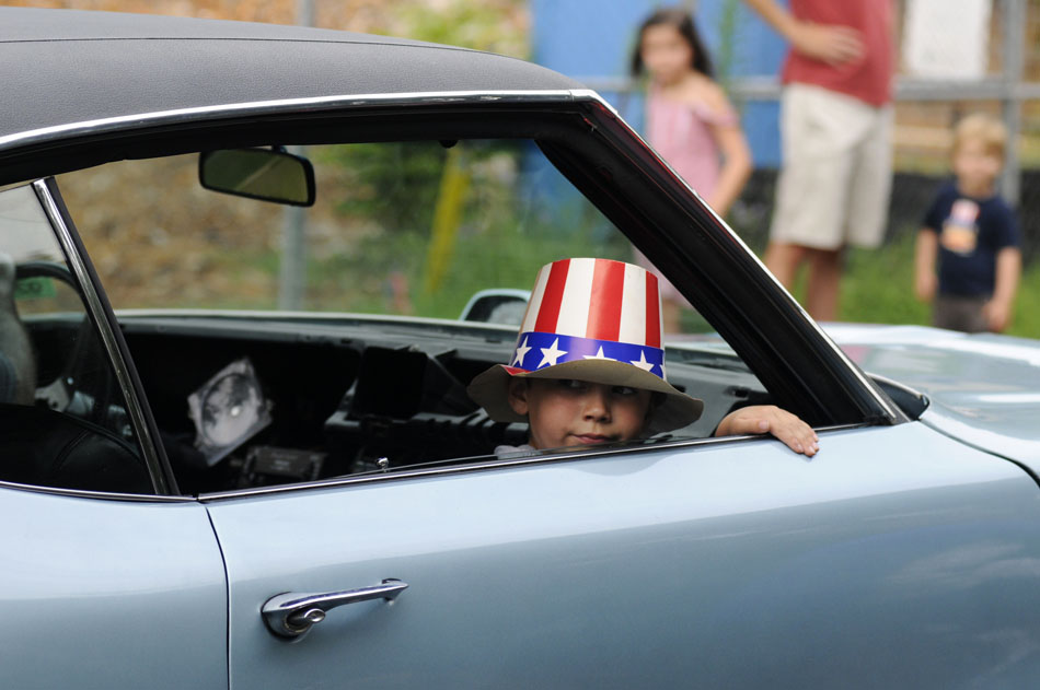 Michael Allen, age 6, looks back at the crowd assembled for the Tarrytown Fourth of July parade as he rides in his father's 1972 Buick Skylark Gran Sport on Saturday, July 3, 2010.