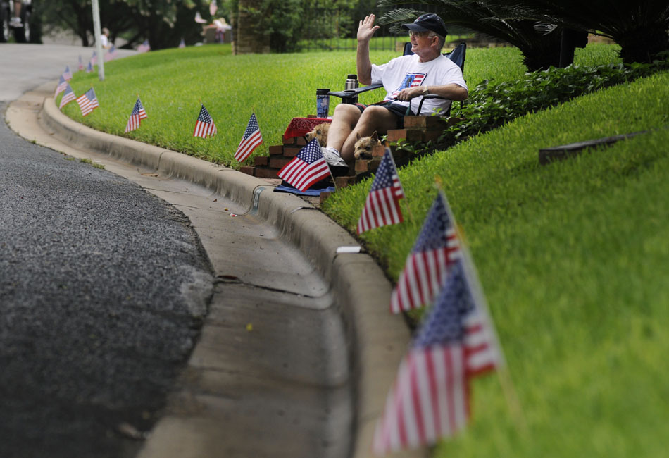 Rick Smith waves to participants in the Tarrytown Fourth of July Parade from the sidewalk in front of his home on Saturday, July 3, 2010.