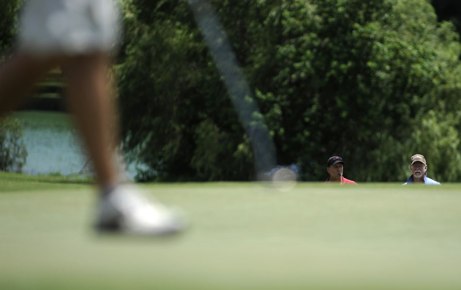 Two spectators watch as members of the final group putt a green during the final round of the Austin City Golf Championship at Jimmy Clay Golf Course on Sunday, Aug. 8, 2010.