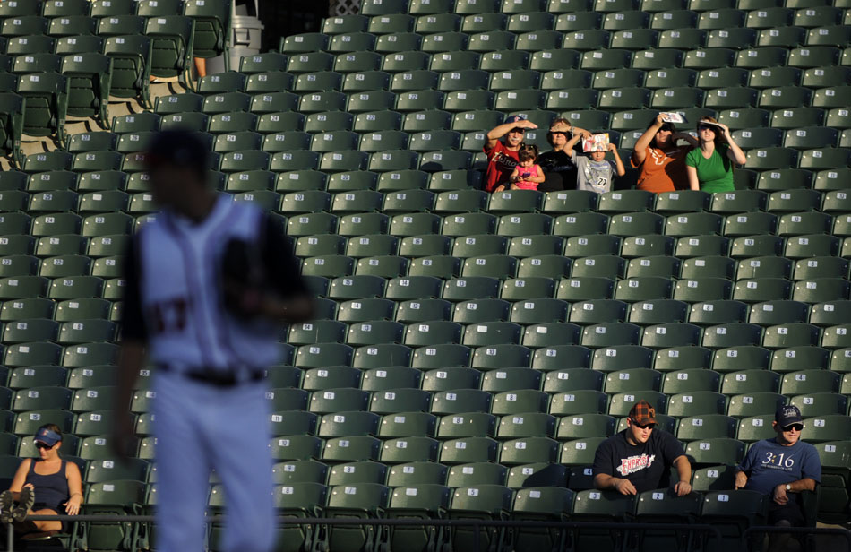 A few fans shade their eyes from the setting sun as Express pitcher Jordan Lyles, age 19, takes the mound to face a Sacramento batter during a game at Dell Diamond on Tuesday, Aug. 10, 2010.