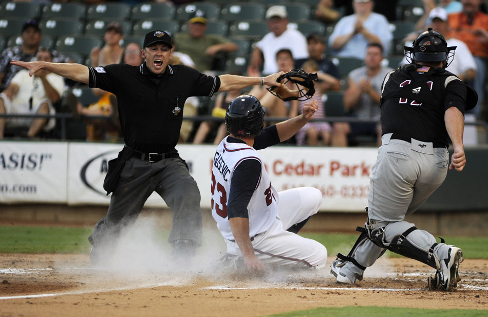 Home base umpire Mike Lusky signals safe as Express first baseman Brian Bogusevic (23) slides into home plate, scoring Round Rock's first run in a game against Sacramento at Dell Diamond on Tuesday, Aug. 10, 2010.