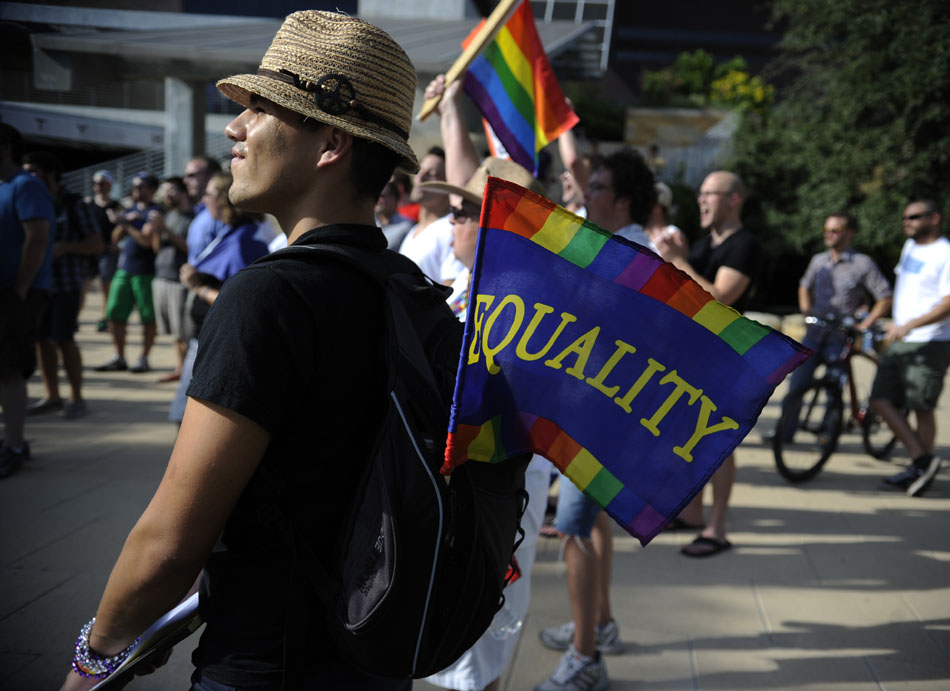 A gay  rights activist carries an equality flag in his backpack as he listens at a rally for gay marriage rights at Austin City Hall on Wednesday, Aug. 4, 2010.