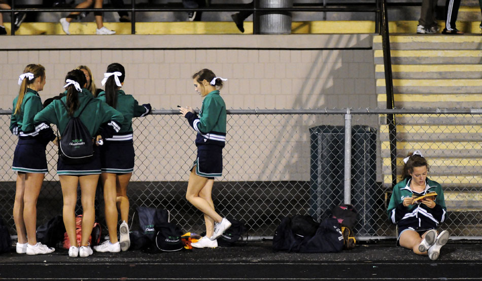 "Peoria Notre Dame cheerleader Cassie Frow, right, reads ""A Tale of Two Cities"" by Charles Dickens during halftime in a game against Quincy Notre Dame on Thursday, Sept. 16, 2010, in Peoria. Frow was reading for a quiz on Friday morning."