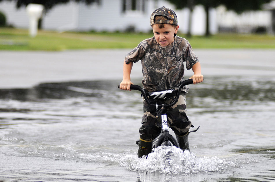 Jared Oest, age 6, navigates his bicycle through a large puddle of deep water with his brother, not pictured, on Thursday, Sept. 2, 2010, in a parking lot at Midwest Central High School in Manito, Ill. Several streets and parking lots in the village were flooded following a severe thunderstorm that pounded the area with high winds and heavy rain on Thursday afternoon.