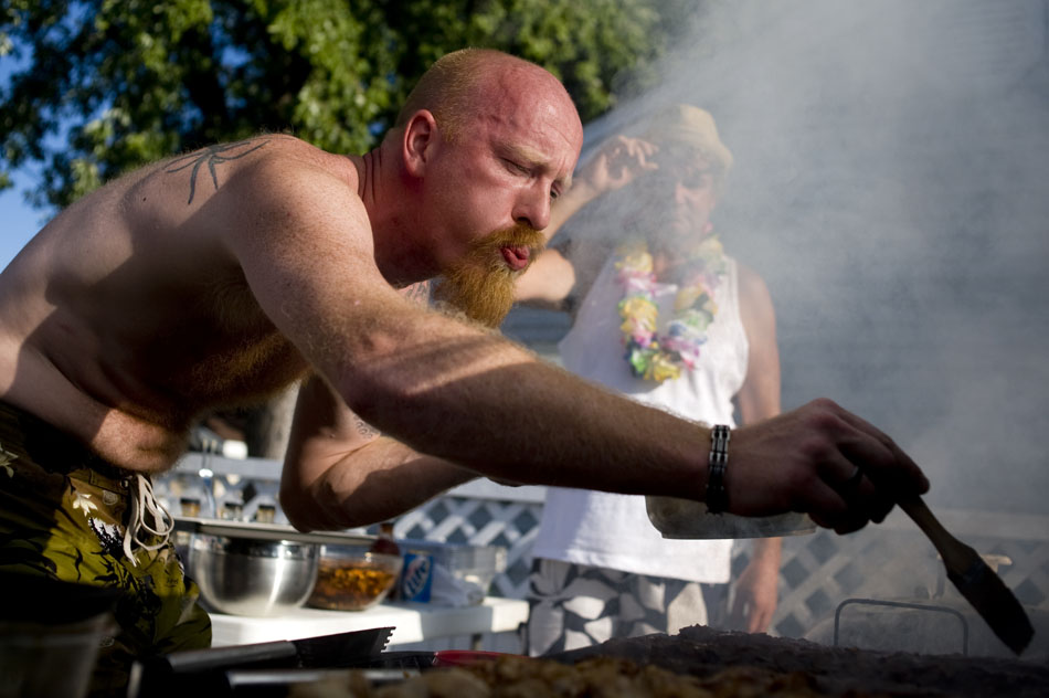 Luke Merrill blows some smoke out of the way so he can find his ribs to baste them during a ribs cookoff on Sunday, Sept. 12, 2010, in Peoria Heights. The annual event pits a few friends against each other for bragging rights and a grilling fork.