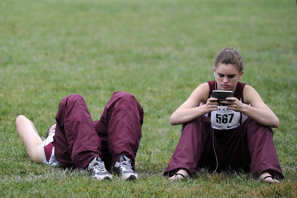 A sends a text message with her phone between races during the Woodruff Cross Country on Saturday, Sept. 11, 2010, in Detweiller Park.
