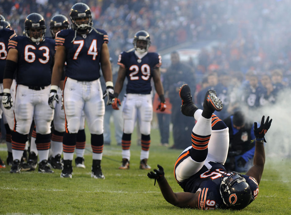 Chicago Bears defensive tackle Anthony Adams (95) tumbles as he makes his way onto the field during player introductions before a game on Sunday, Nov. 28, 2010, at Soldier Field in Chicago.