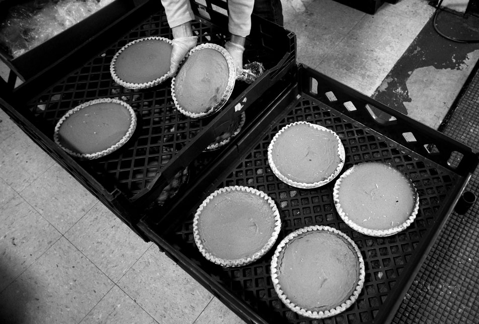 A volunteer unwraps pumpkin pies as they are prepared to be sliced into pieces and delivered as part of a Thanksgiving meal for the needy on Thursday, Nov. 25, 2010, at the South Side Mission.