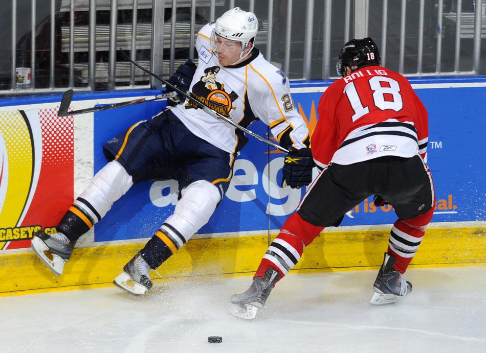 Rockford's Brandon Bollig (18) checks Peoria's Ian Cole into the glass during a game on Sunday, Nov. 21, 2010, at Carver Arena.