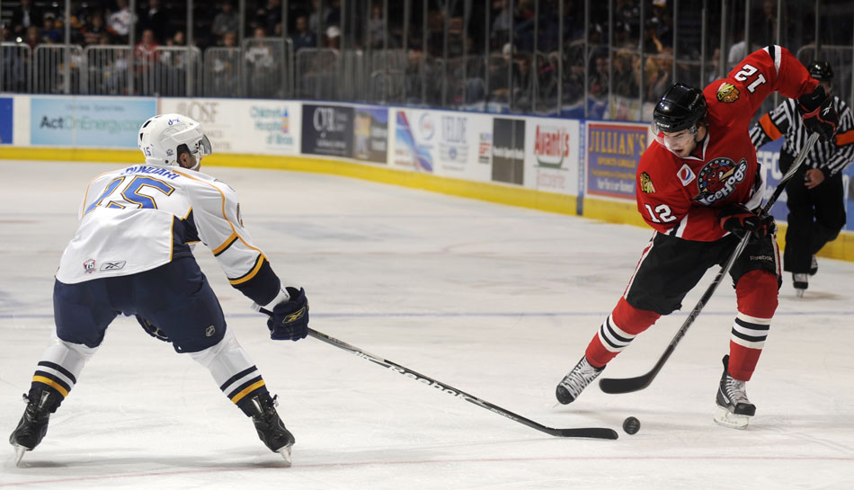 Rockford's  Kyle Beach (12) lines up for a shot in front of Peoria's Mark Cundari during a game on Sunday, Nov. 21, 2010, at Carver Arena.