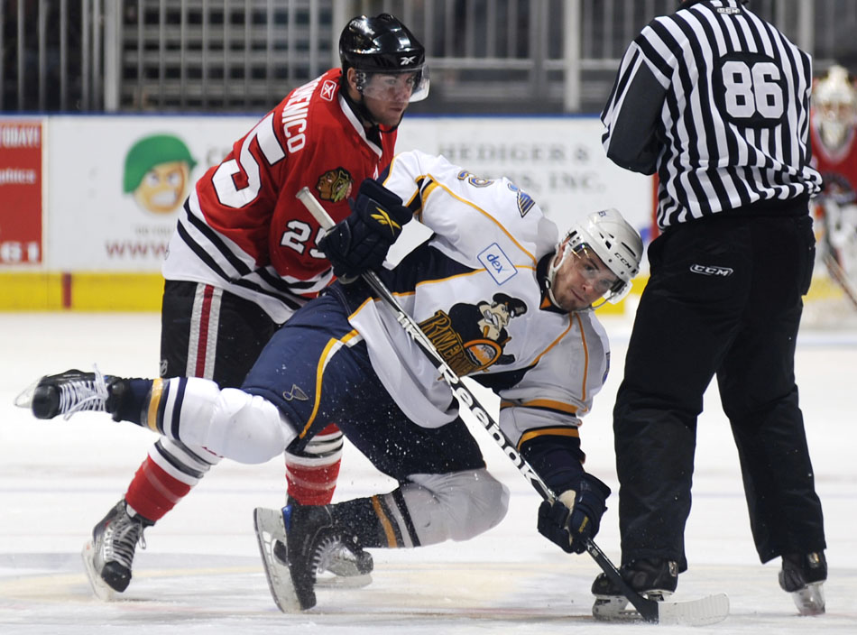 Peoria's Brett Sonne, right, falls to the ice after contact from Rockford's Chris DiDomenico during a game on Sunday, Nov. 21, 2010, at Carver Arena.