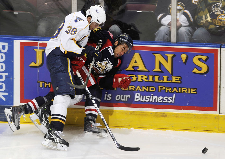 Peoria Rivermen right wing Ryan Reaves (38) checks Grand Rapids Griffins left wing Jordan Owens into the boards during a game on Saturday, Dec. 11, 2010, at Carver Arena.