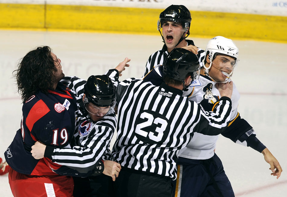 Referees separate Peoria Rivermen right wing Ryan Reaves, right, and Grand Rapids Griffins defender Greg Amadio (19) after a fight in the opening minutes of a game on Saturday, Dec. 11, 2010, at Carver Arena.