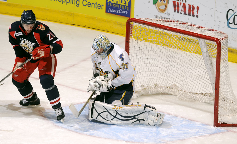 Peoria Rivermen goalie Ben Bishop makes a save in front of Grand Rapids Griffins defender Brandon Straub (20) during a game on Saturday, Dec. 11, 2010, at Carver Arena.