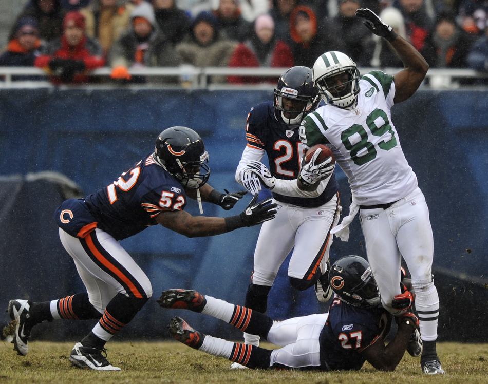 New York Jets wide receiver Jerricho Cotchery (89) tries to break away from Chicago Bears' Major Wright (27), Corey Graham (21) and Brian Iwuh (52) during a game on Sunday, Dec. 26, 2010, in Chicago. Chicago won 38-34.