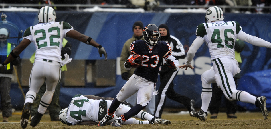 Chicago Bears wide receiver Devin Hester (23) eludes New York Jets' James Ihedigbo (44), Brodney Pool (22) and Tanner Purdum (46) on a punt return during a game on Sunday, Dec. 26, 2010, in Chicago. Chicago won 38-34.