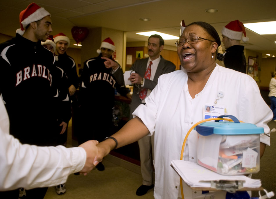 """Mae Roberts, a nurse at Methodist Hospital, reacts as she meets Dave Snell, the Bradley play-by-play announcer, as the men's basketball team visits patients on Thursday, Dec. 16, 2010, at the hospital. """"I feel weak in the knees,"""" she said before receiving an autograph from Snell."""