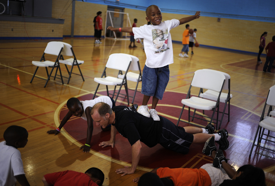 Larenz Dempz, age 7, tries to keep his balance as he stands on Brian Beavliev's back during a push up at the East Boys and Girls Club in Austin on Wednesday, June 16, 2010. Area youngsters participated in a Police Activities League basketball camp at the gymnasium.