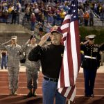Terry Hicks, of Galsburg, Ill., salutes as taps are played to honor former East Peoria High School students who have been killed in the military during patriotic night ceremonies before a East Peoria-Washington football game on Friday, Sept. 10, 2010, in East Peoria. Hicks served with the Army in Vietnam.