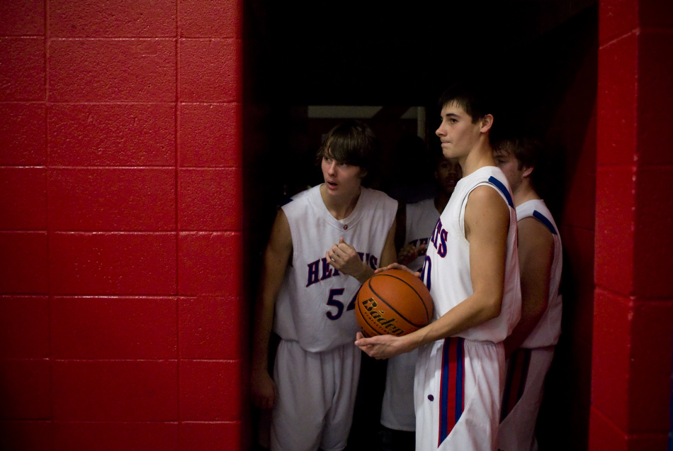 Peoria Heights' Zach Wilson (54) peeks out at the court as teammate Jon Lowry, right, holds the ball ready to lead the team out of the locker room before a game against Beardstown on Friday, Dec. 3, 2010, in Peoria Heights.