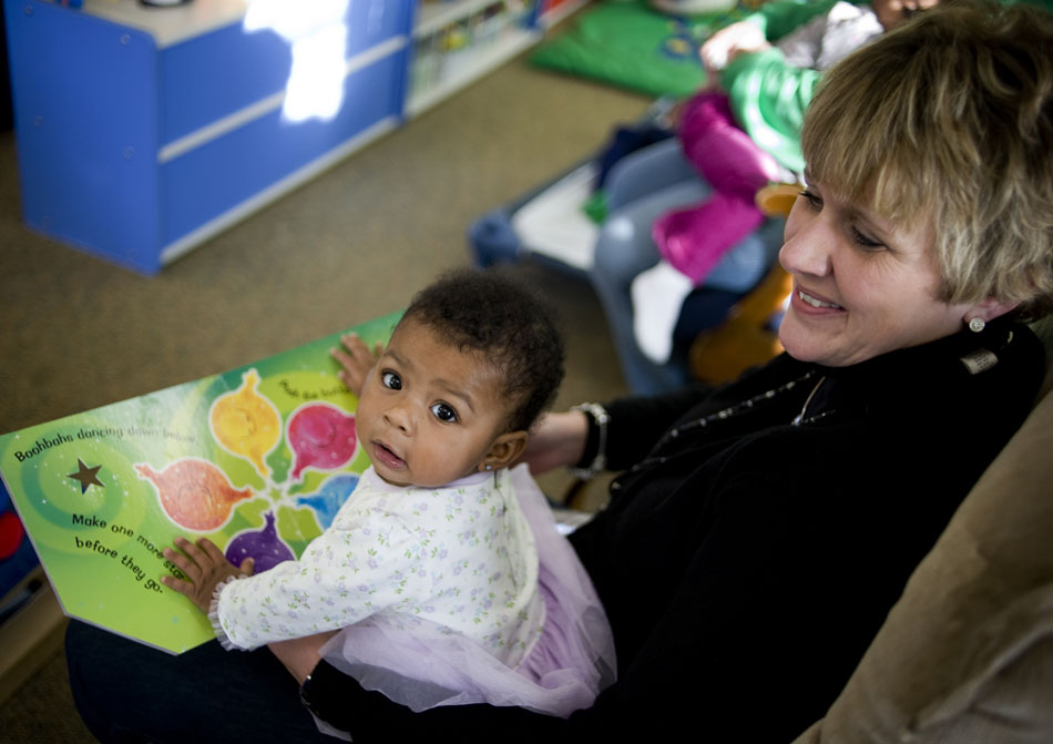Zyriah Ellis, 5 months old, looks back as Donna Ashley, director of the Crittenton Centers Crisis Nursery in Peoria, reads a book to the youngster on Friday, Dec. 31, 2010, at the nursery. The center is in need of volunteers to help care for the children at the nursery, said Ashley, who was one of a handful of employees manning the nursery without volunteers on Friday.