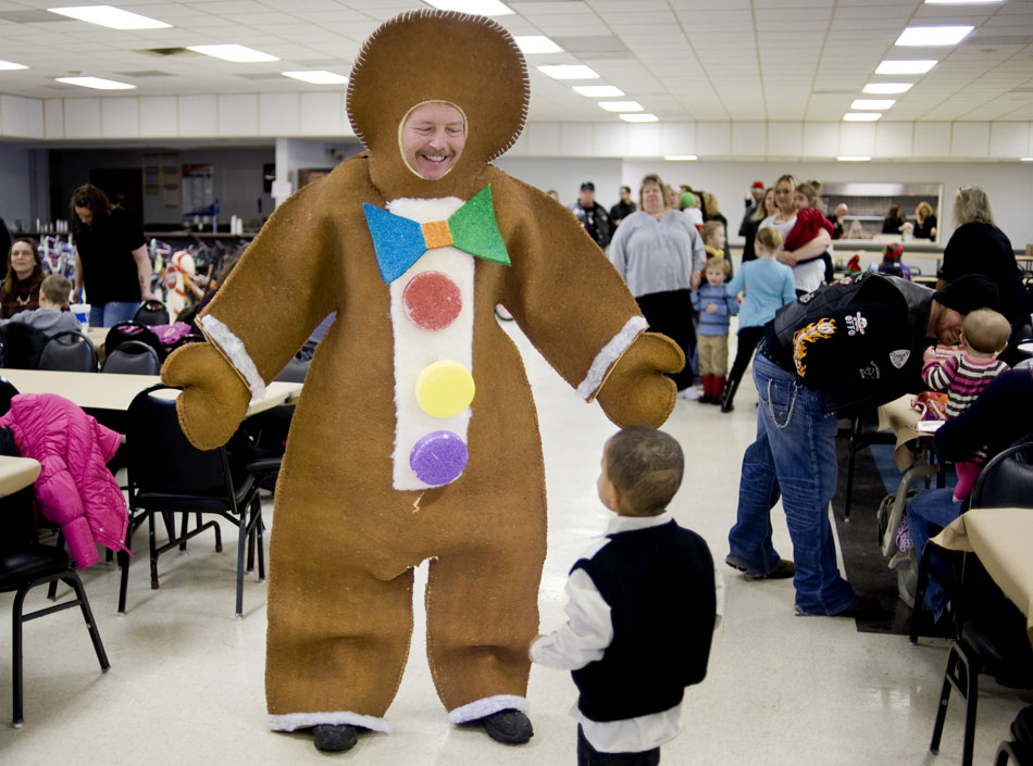 Gingerbread man Carl Duckwiler interacts with a youngster during a Christmas party hosted by the Outlaws Peoria motorcycle club on Saturday, Dec. 18, 2010, at Itoo Hall. Duckwiler said has been dressing up in gingerbread after the costume won a Christmas party contest a few years back. The annual Outlaws party is in it's 28th year, and organizers said it will provide individual toys to 305 needy children this year.