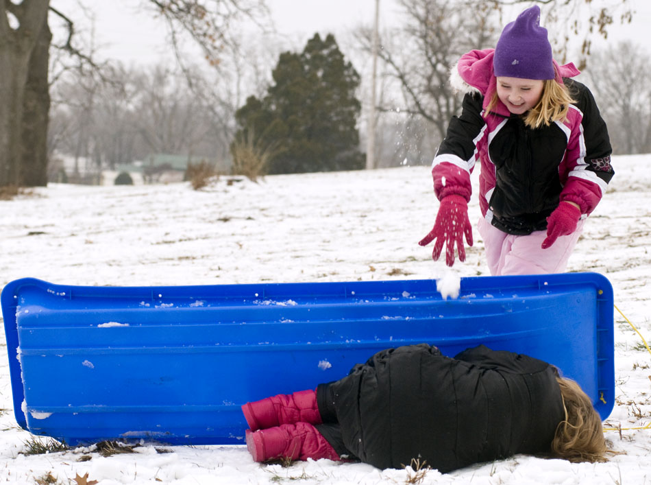 Despite her best effort to hide behind her sled, Chloe McCabe, age 9, still gets pummeled by a snow ball from Evie Fornoff, age 8, during a winter break camp for kids out of school for the holidays on Tuesday, Dec. 21, 2010, in Pekin, Ill. Temperatures in the mid 30s made for ideal sledding, snow ball fighting and snowman building conditions for the youngsters.