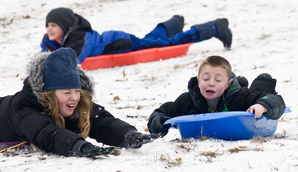 Gavin Richardson, right, age 7, reacts as his sled collides with Tia Parker's sled during a winter break camp for kids out of school for the holidays on Tuesday, Dec. 21, 2010, in Pekin, Ill.