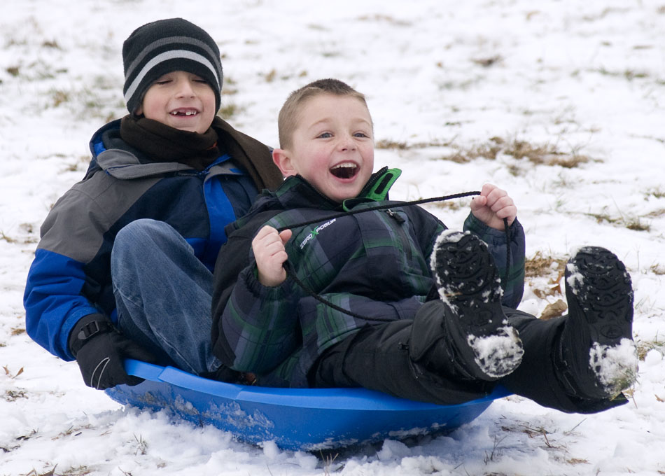 Gavin Richardson, right, age 7, reacts as he gains some speed on a sled with Mason Graber, age 7, during a winter break camp for kids out of school for the holidays on Tuesday, Dec. 21, 2010, in Pekin, Ill.