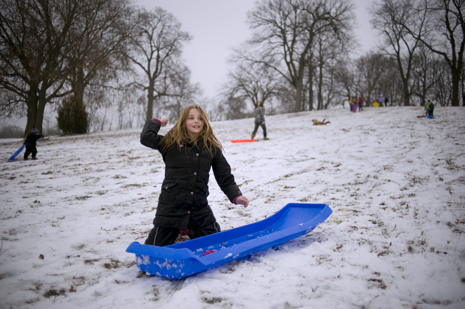 Chloe McCabe, age 9, throws a snowball during a fight with a friend at a winter break camp for kids out of school for the holidays on Tuesday, Dec. 21, 2010, in Pekin, Ill.