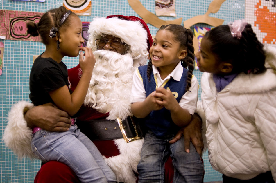 Tierney Johnson, left, age 6, ponders what she wants for Christmas as she talks with Santa Claus along with Andre Thomas, age 4, and Alexis Ross, age 6, during the Red Stocking Party on Saturday, Dec. 11, 2010, at Manual High School.
