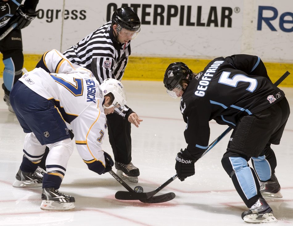 The official drops the puck for a face off between Peoria Rivermen center T.J. Hensick (7) and Milwaukee Admirals center Blake Geoffrion (5) during a game on Sunday, Dec. 5, 2010, at Carver Arena.