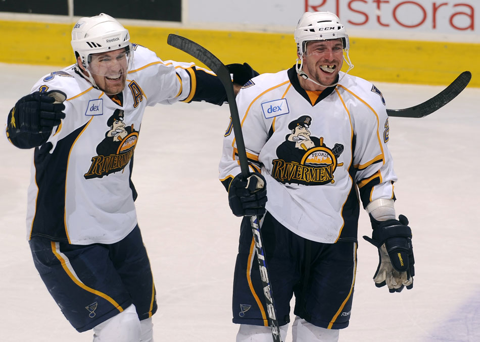 Peoria Rivermen right wing Graham Mink, left, celebrates with teammate Peoria Rivermen defender Nathan Oystrick after Oystrick scored a goal late in the third period of a game against Milwaukee on Sunday, Dec. 5, 2010, at Carver Arena.
